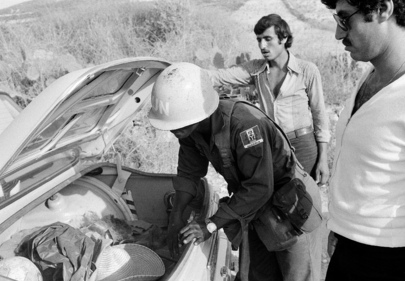 Nigerian UNIFIL soldier inspects the trunk of a car in war-torn Lebanon,1978