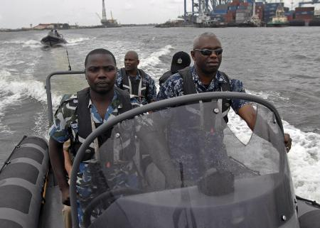 A Nigerian Navy SBS commando(l) in a Rigid Hull Inflatable Boat. Beside him is a US Navy Commander