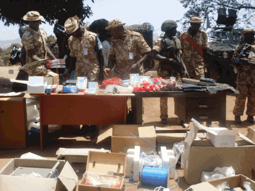 Troops of the Special Task Force -Operation Safe Haven inspect seized bomb-making materiel. In the background is an OTOKAR COBRA APC