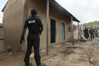 An operative of the State Security Services, Nigeria's secret police raids a bomb-making factory