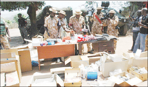 Seized bomb-making materiel. In the background, a mine-resistant Otokar Cobra APC