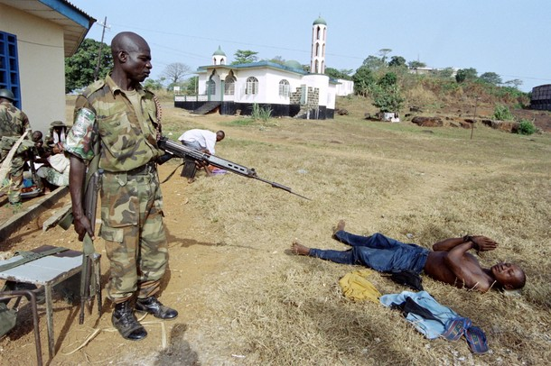 Nigerian ecomog soldier keeps watch over a captured rebel loyal to