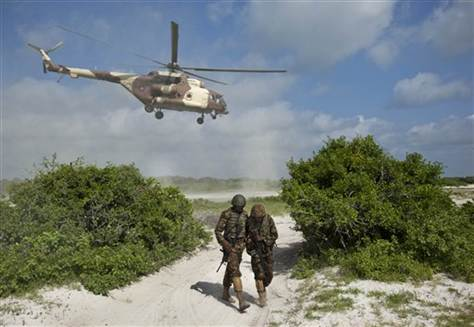 Kenyan troops under the shadow of a Kenya Air Force Mi-171e helicopter