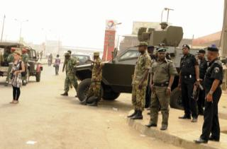 Nigerian soldiers stand around a 4WD and an Otokar Cobra APC, as cops in black tunics look on
