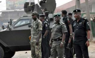 Soldiers and black-shirted cops stand close to an Otokar Cobra APC