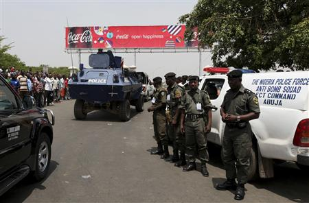 Men of the Nigeria Police Anti-Bomb Squad watch as a mine-protected Otokar Cobra APC drives past