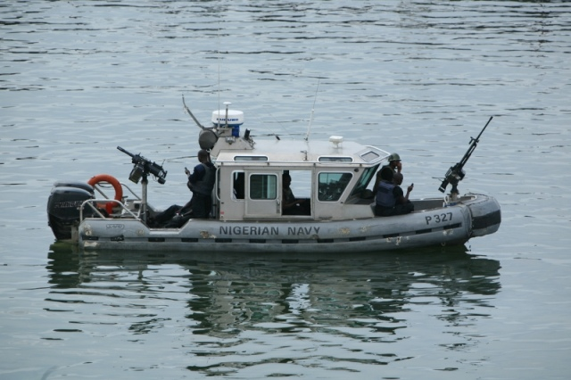 Nigerian Navy SBS commandos patrol in a RBS Defender boat with a 12.7mm HMG fore and a 40mm AGL aft