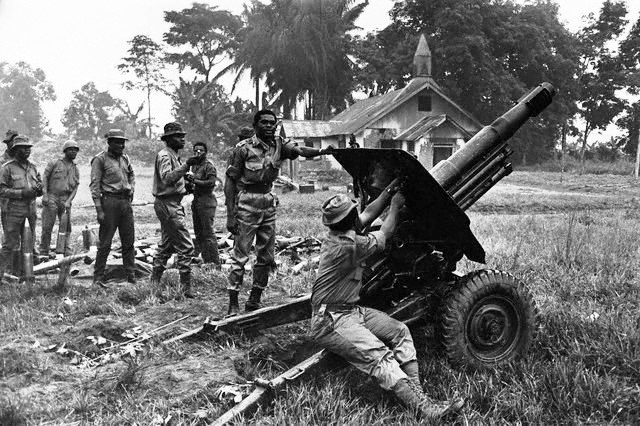 Pioneer GOC 3 Div,Colonel B.Adekunle(hand on howitzer)watches a gunner during the Nigerian Civil War