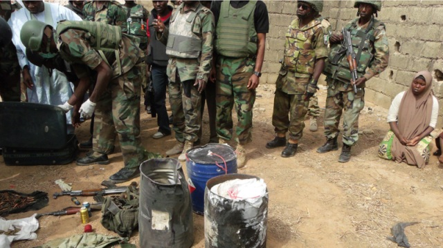 A JSTF Combat Engineer defuses IEDs elsewhere in Kano, as counterinsurgency troops observe his work