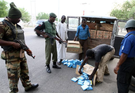 JSTF combined forces - soldier(l), MOPOL(c) and seaman(r) search a vehicle at Maiduguri