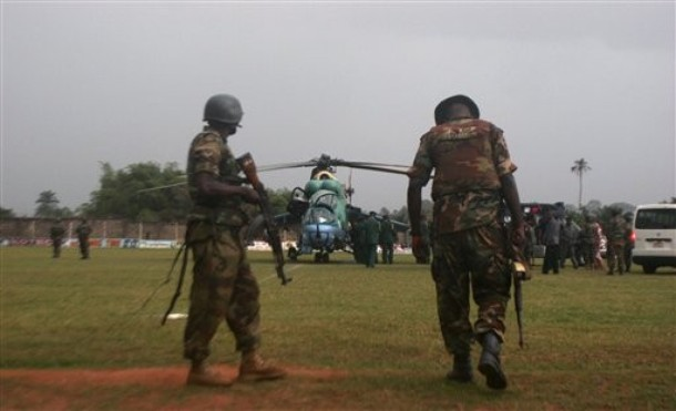 Nigerian Army troops witness the landing of a Nigerian Air Force Mi-24 Hind attack helicopter