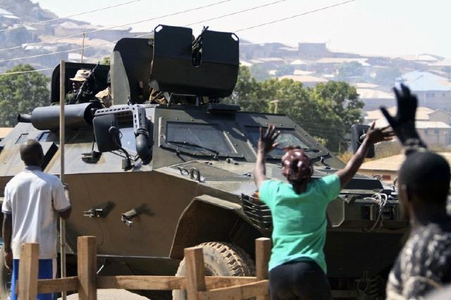 FINAL SOLUTION: Appreciative Nigerians wave to troops inside  an Otokar Cobra APC in a conflict zone