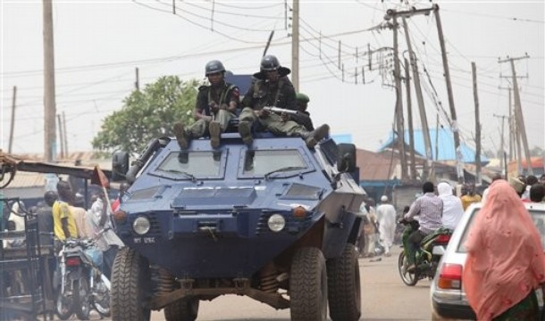 Men of the Police Mobile Force(MOPOL) advance atop an Otokar Cobra APC