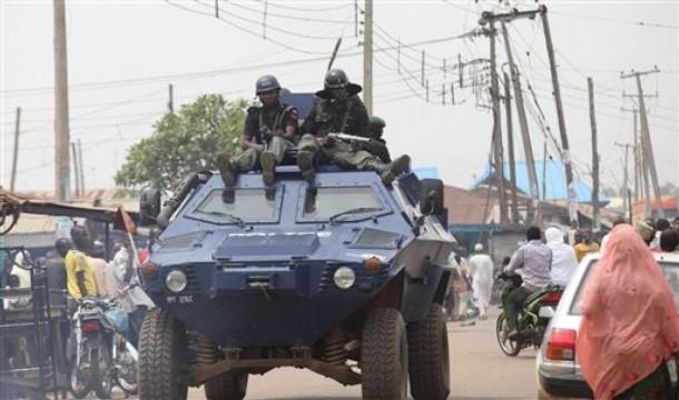 Men of the Police Mobile Force(MOPOL) advance atop an Otokar Cobra APC