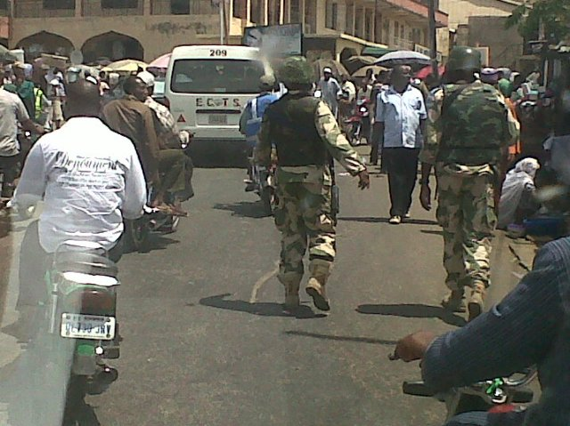 Troops dismount for a defiant foot patrol in the busy Central Market at the flashpoint town of Okene