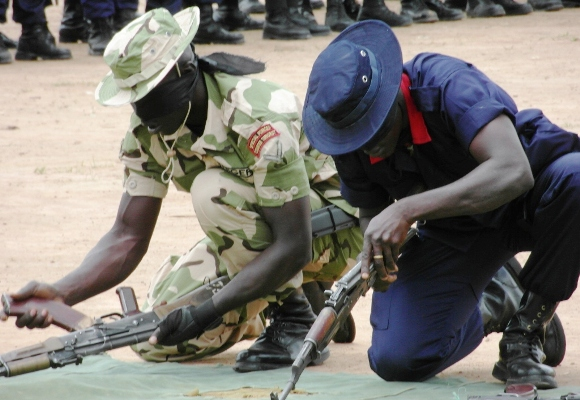 Soldier and Civil Defender strip and reassemble their weapons at the CTCOIN Centre, Kachia