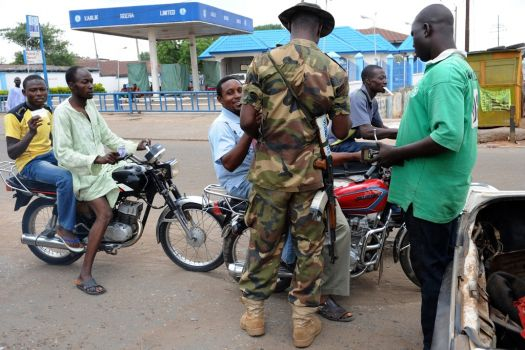 A Nigerian soldier checks motorcyclists to stave off ride-by attacks by urban terrorists