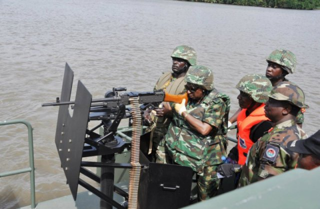 Minister of State(Defence),Mrs Obada tests a GPMG while Brig.Gen Golau and Army Special Forces watch