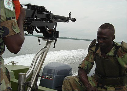 Nigerian Army Amphibious Forces patrol in a river gunboat armed with a DShk 12.7mm machine gun