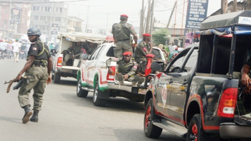 A Police Mobile Force(MOPOL)cop walks while red berets of the Anti Terrorism Squad ride in a 4WD van