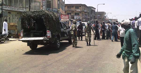 Nigerian troops and a 4WD van at the scene of a suicide bomb attack