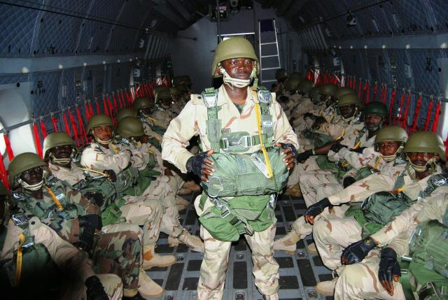 Male and female paratroopers of the Nigerian Army prepare to jump off a G222 plane of the Nigerian Air Force
