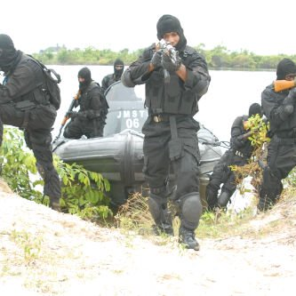 SBS commandos emerge from the water in a RHIB