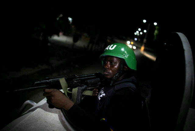 A Nigerian MOPOL cop on nighttime CTCOIN patrol inside an APC in Mogadishu