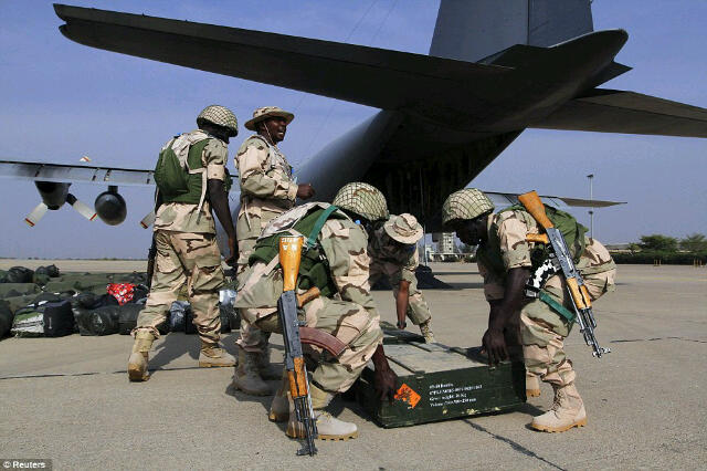 Mali-bound troops conduct final checks in the shadow of a Nigerian Air Force C130-H30 at Kaduna