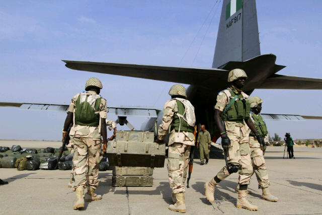Nigerian soldiers in the shade of a Mali-bound Nigerian Air Force C130 Hercules plane