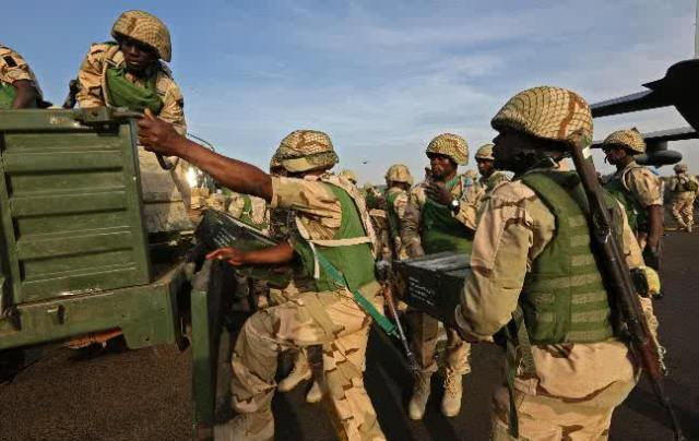 Nigerian troops board vehicles at Bamako Airport