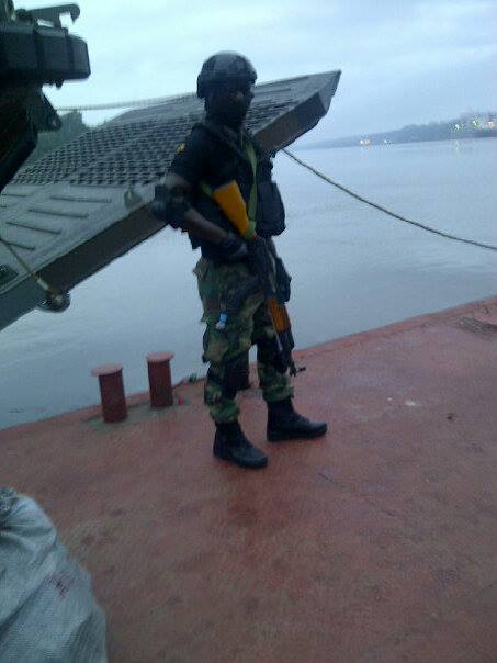 A Nigerian Army Special Forces commando poses beside a landing craft